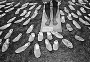 Canvas shoes displayed on grass, in front of shoeless vendor. Glastonbury 1992