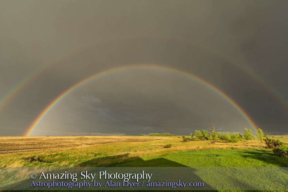 A classic double rainbow as a storm receded, on June 2, 2012, taken from home. The rainbow lasted only briefly. Note the brighter sky interior to the rainbow and the dark sky between the rainbows, called Alexander's Dark band. This was taken with an 10-22mm lens at 10mm to take in all of the rainbow. Canon 60Da camera.