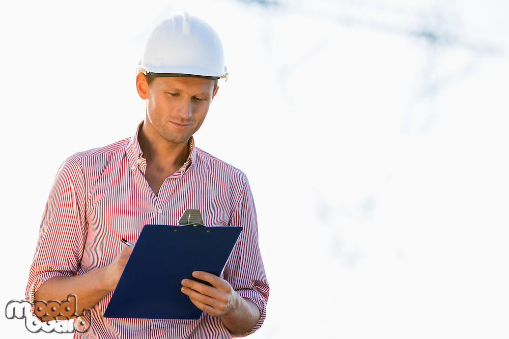 Male architect writing on clipboard at site