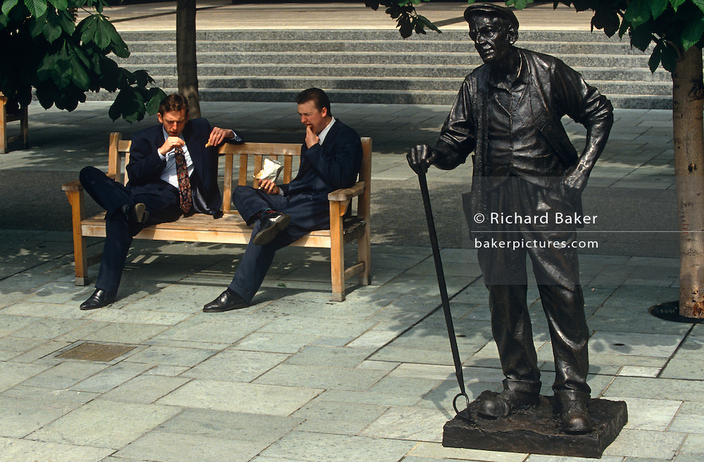 Two young men dressed in office suits casually stuff their lunches during a hot lunchtime break in the Broadgate Estate in the City of London. Both with legs across knees, the lads in their 20s sit on a bench beneath a tree alongside the statue of a traditional gardener, slightly bent and equipped with hoe and wearing a wastecoat, hobnailed boots and flat cap, an iconic salt-of-the-earth workman. This scene suggests the social divisions of the working man: Of the young, educated post-war generation whose opportunities have afforded them a faster lifestyle, far removed from that of the physically-exhausted man whose life has been spent working the honest land.  The English social divide is clearly represented here as the harshness of the manual labourer versus the youth of today, seen in the middle of the modern city.