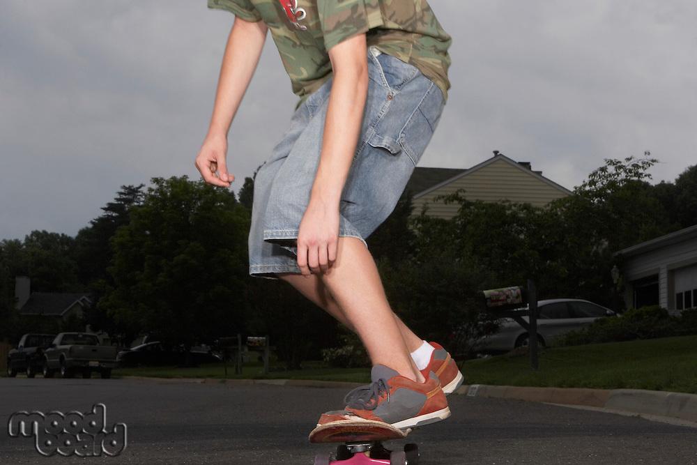 Teenage boy (16-17) skateboarding on street low section