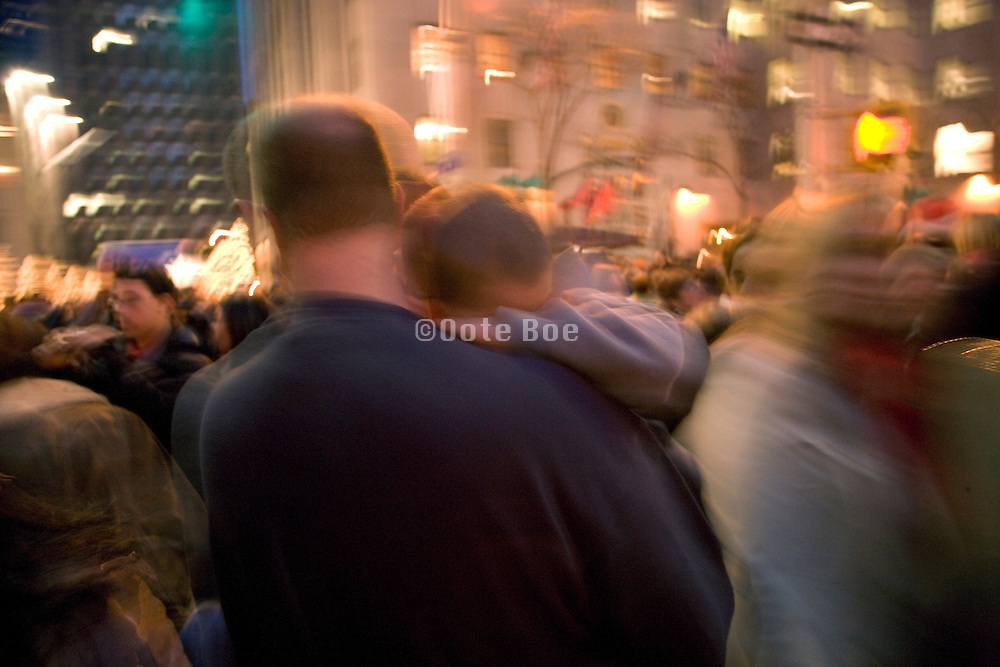 a little boy tired and carried by his father while walking in a big crowd in New York City