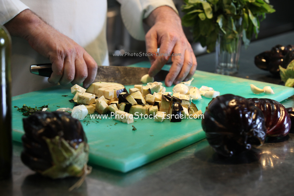 Hands of a cook preparing salad dicing eggplant