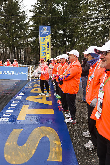 course monitors stand at start line on wet morning in Hopkinton