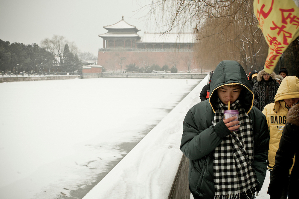 Young Chinese tourists walking along the moat of the Forbidden city after a snowfall that local authorities say they have artificially provoked by the Chinese Control Meteo Office to fight an exceptional drought in the northern China. February 10 2011