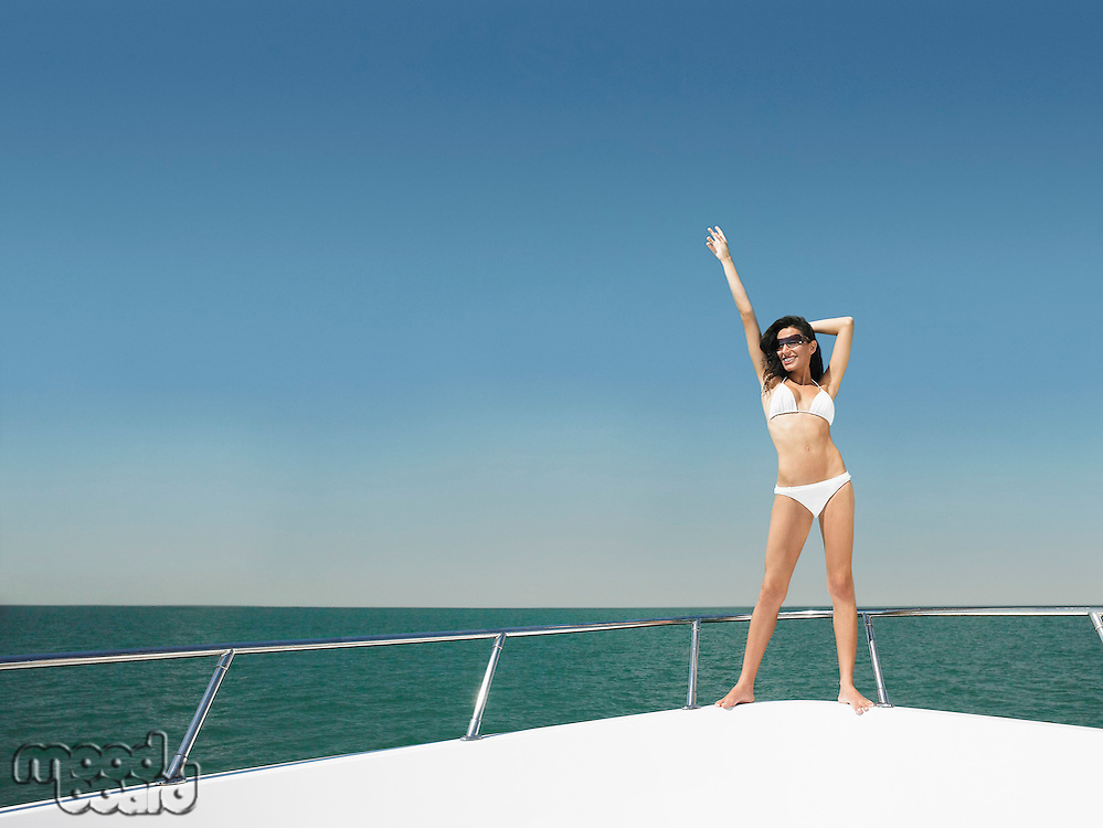 Young woman in bikini standing on bow of yacht with arm outstretched portrait