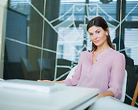 Portrait of confident young businesswoman at conference table