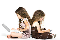 caucasian little girls playing game console back to back isolated studio on white background
