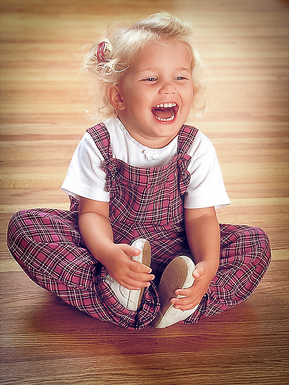 Small child laughing seated on floor