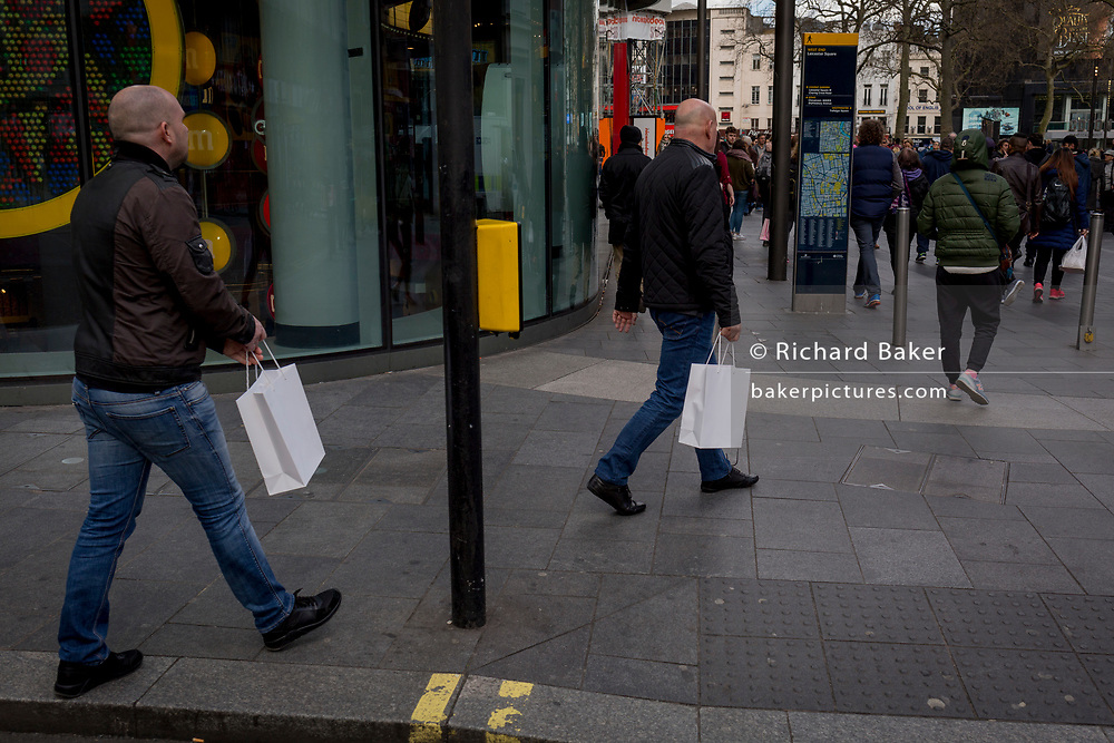 Two bald men each carrying identical white bags walk past the M@M store in Leicester Square, on 21st March 2017, in London, England.