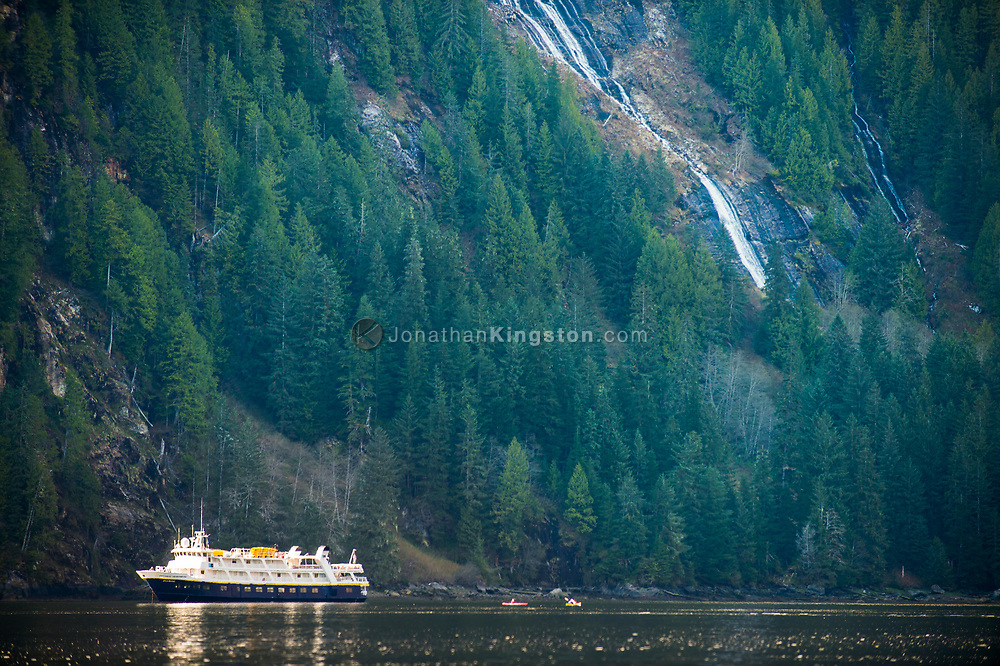 A small cruise ship underneath a massive waterfall in Misty Fjords.