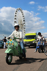 © Licensed to London News Pictures. 23/08/2014. Brighton, UK.  Participants in the Brighton Mod Weekend ride along the seafront on August Bank Holiday weekend. Temperatures in the UK are expected to be lower than normal for this time of year.. Photo credit : Hugo Michiels/LNP