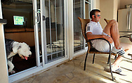 Dustin Johnson with his dog Max, relaxes at his Myrtle Beach home. Johnson has a chance to win the FedExCup Playoffs title this weekend, he's currently No. 2 in the standings entering the Tour Championship playoff finale, then he heads to his first Ryder Cup the next week in Wales.