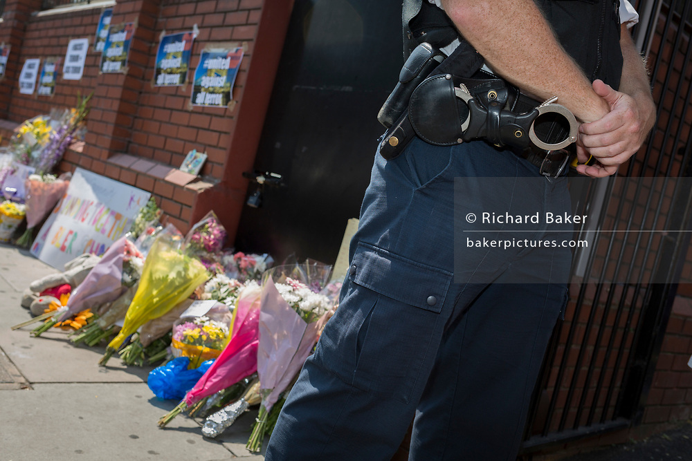 Following the attack on a group of Muslim men outside the Finsbury Park mosque which killed one person and seriously injured another ten, met police officers guard the Islamic building where flowers have been left, on 19th June 2017, in the borough of Islington, north London, England.