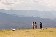 Tourists view the Valley of Oaxaca from Monte Albán pre-Columbian archaeological site in the Santa Cruz Xoxocotlán, Oaxaca, Mexico.
