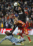 Sporting Kansas City forward C.J. Sapong, bottom, is defended by Real Salt Lake defender Nat Borchers, center as Real Salt Lake goalkeeper Nick Rimando, top, grabs a corner kick during the second half of the MLS Cup final soccer match in Kansas City, Kan., Saturday, Dec. 7, 2013. (AP Photo/Colin E. Braley)