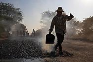 A worker is puoring tar on a road in Myanmar.