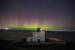 The Northern Lights, or Aurora Borealis appear in the sky over Bamburgh lighthouse at stag Rock in Northumberland.