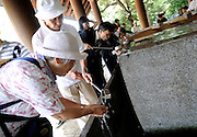 Pilgrims drink and wash their hands at a fountain prior to praying during events to commemorate the end of World War II  at Yasukuni Shrine in Tokyo, Japan on 15 Aug. 2008. Wartime prime minister Hideki Tojo - who ordered the attack on Peal Harbor and was charged and hanged as a war criminal after World War II, is enshrined inside the controversial Yasukuni Shrine together with 13 other convicted war criminals, a fact that still angers citizens in China and South Korea, both of which fell vicim to Japan's wartime activities. Aug 15. is the anniversary of Japan's surrender in World War II and 100s of thousands of pilgrims from around the country visit the shrine...Photographer: Robert Gilhooly