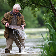 "VINCE THURKETTLE PANNING IN A RIVER IN NORFOLK...Britain is experiencing a gold rush with record numbers turning to prospecting to beat the credit crunch...Full-time gold-panner Vince Thurkettle said more people than ever before are heading to the UK's rivers in search of precious nuggets and flakes...Demand for his gold-panning courses has more than trebled in the last year driven by the deepening recession and the high price of gold...""In the last 12 months people have suddenly shown much more interest in buying, selling and finding gold,"" he said...""Before a lot of people didn't seem to believe there was gold to be found in Britain's rivers...""But now everyone knows the price of gold has gone up and suddenly due to the credit crunch more people are trying their hand at gold-panning.""..The UK's last gold rush was in Kidonnan in Scotland in 1869 when a gold-panner struck lucky in the River Helmsdale...Within months hundreds of hopefuls had descended on the normally deserted Scottish Glen...But the prospectors left within three years and for decades gold-panning in Britain was seen by most as merely a hobby...Now adventurers in need of extra cash are once more heading to the hills of Scotland and Wales in search of treasure...SEE COPY CATCHLINE Britain's gold rush"