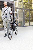 Businessman with bicycle standing outside office building