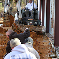 Jason Jordan, with Jordan Plumbing in New Albany, runs the backhoe as he digs out a trench for piping at the new Eight Days of Hope Headquarters being built in Pontotoc on Monday morning. Jordan Plumbing is donating their time to see that all the plumbing is installed.