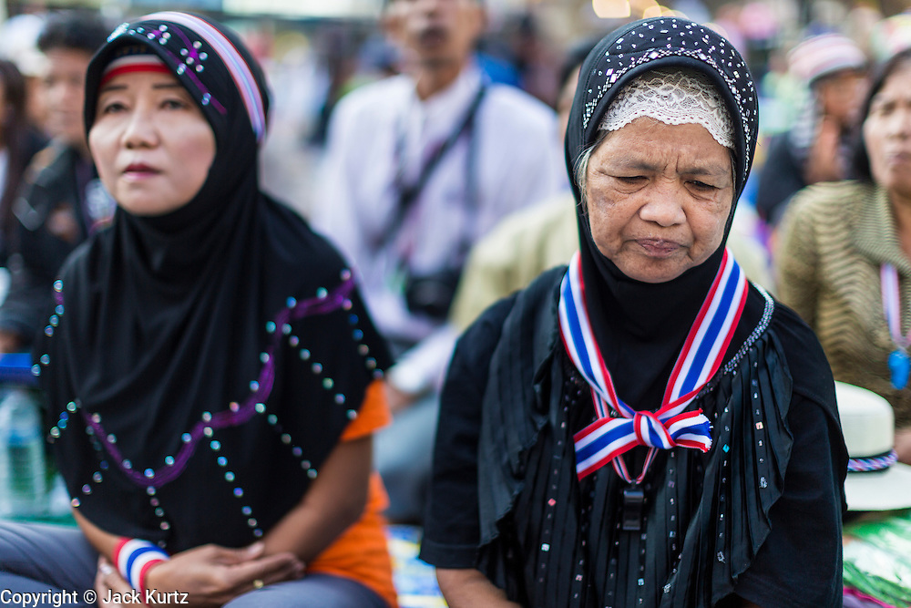 """15 JANUARY 2014 - BANGKOK, THAILAND: Thai Muslim women pray during morning prayers at the main stage for Shutdown Bangkok. Wednesday morning prayers were led by Buddhist monks, Muslim imams and a Catholic priest. Tens of thousands of Thai anti-government protestors continued to block the streets of Bangkok Wednesday to shut down the Thai capitol. The protest, """"Shutdown Bangkok,"""" is expected to last at least a week. Shutdown Bangkok is organized by People's Democratic Reform Committee (PRDC). It's a continuation of protests that started in early November. There have been shootings almost every night at different protests sites around Bangkok. The malls in Bangkok are still open but many other businesses are closed and mass transit is swamped with both protestors and people who had to use mass transit because the roads were blocked.    PHOTO BY JACK KURTZ"""