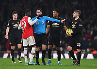 Football - 2019 / 2020 Premier League - Arsenal vs. Manchester United<br /> <br /> Referee Chris Kavanagh with Arsenal's Nicolas Pepe and Manchester United's Luke Shaw, at The Emirates Stadium.<br /> <br /> COLORSPORT/ASHLEY WESTERN