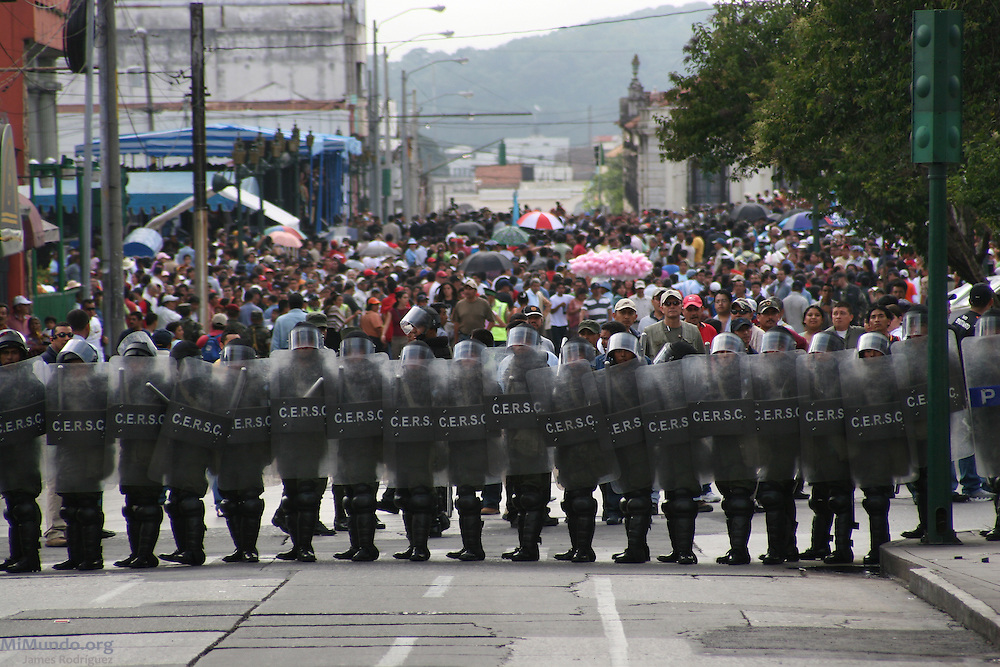 Anti-riot police block the path of the March for Remembrance eastbound on 6th Street in Zone 1 as the Military Day festivities are being held simultaneously a block away in Guatemala City's central park. Organized by H.I.J.O.S. (Sons and Daughters for Identity and Justice Against Forgetfulness and Silence), the March for Remembrance is a counter march to the annual Military Day parade, seen by many as inadequate in modern Guatemala considering the atrocities carried out by the institution against the local population during the 36-year internal armed conflict. Guatemala City, Guatemala. June 30, 2007.