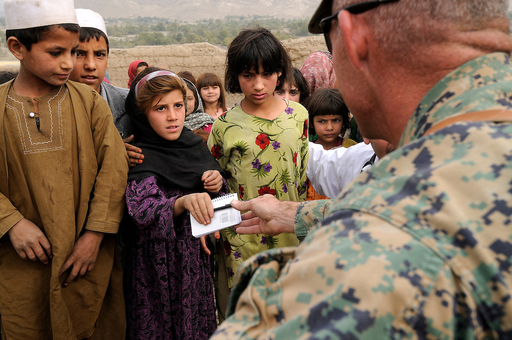 """US Marine Colonel Jeff Haynes, Commanding Officer, 201st Regional Corps Advisory Command, hands pens and note books to children in Tagab Valley during an operation.....To win a counterinsurgency, Haynes says you have to transform the environment and set conditions for change.  If people see there is hope, something worth them risking their lives for, then an army can win.  He says, """"You win them over, and they facilitate security pointing out the enemy. It is a symbiotic relationship.""""  ...."""