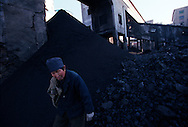 A worker at the state run Jinhuagong coal mine sorts coal outside the mine. Seven of the world's ten most polluted cities are in China due primarily to China's dilapidated heavy industries and its dependence on coal - the dirtiest form of energy. 75% of China's growing energy needs comes from coal. ..Dàtóng, Shanxi Province, China. 10/11/2005..Photo © J.B. Russell