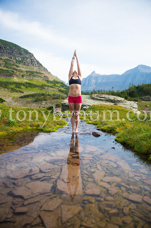 woman doing yoga in mountain stream glacier national park
