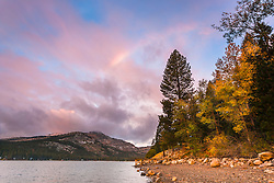 """Rainbow Over Donner Lake 2"" - Photograph of a faint rainbow shot at sunrise, with some fall colors along the shoreline."