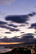 An image from Oahu showing a crescent moon and clouds in front of a darkening sky.