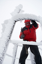 Mount Washington Observatory weather intern Alan Metcalf uses a crowbar to knock rime ice off of the instruments in the weather tower on Mount Washington in New Hampshire's White Mountains.