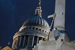 © licensed to London News Pictures. London, UK 01/05/2012. A demonstrator on the monument at Paternoster Square as Occupy London activists occupy parts of the London Stock Exchange and Paternoster Square as part of May Day protests in London. Photo credit: Tolga Akmen/LNP