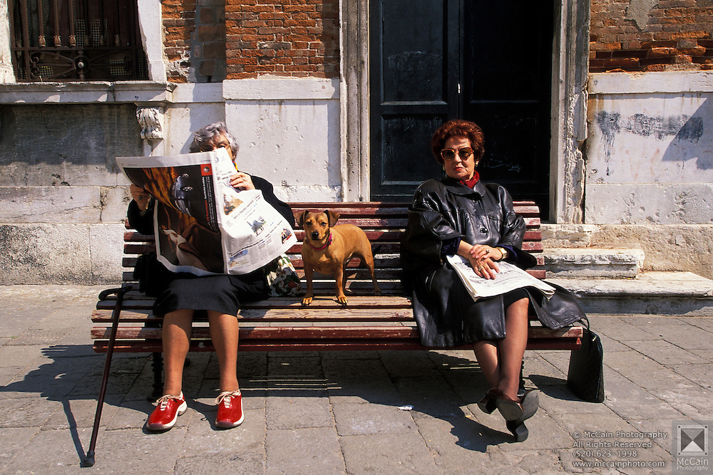 Two women reading newspapers, sitting on bench with dog, Venice, Italy..Subject photograph(s) are copyright Edward McCain. All rights are reserved except those specifically granted by Edward McCain in writing prior to publication...McCain Photography.211 S 4th Avenue.Tucson, AZ 85701-2103.(520) 623-1998.mobile: (520) 990-0999.fax: (520) 623-1190.http://www.mccainphoto.com.edward@mccainphoto.com...