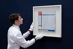 © Licensed to London News Pictures. 14/06/2013. London, UK. A Sotheby's employee adjusts 'Composition with Red, Yellow and Blue' (1927, est. GB£4,500,000-6,500,000) by Dutch painter Peit Mondrian at the press view for a Sotheby's auction in London today (14/06/2013). The Impressionist and Modern Art Evening Sale takes place on the 19th of June 2013 at Sotheby's New Bond Street premises.  Photo credit: Matt Cetti-Roberts/LNP