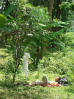 Yung woman lying in tropical forest sunbathing