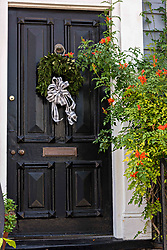 December 21, 2017 - Charleston, South Carolina, United States of America - A Christmas wreath hangs from a wooden door on a historic home along King Street in Charleston, SC. (Credit Image: © Richard Ellis via ZUMA Wire)