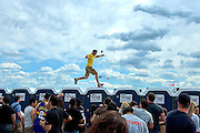 "Beer cans shower a Preakness-goer seen running on top of the portable toilets in Pimlico's infield. The stunt, known by some as ""Running the Gauntlet,"" typically ends with a security escort out of the park."