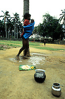 TAMIL NADU, MARCH 1994.A young man chained to a tree is in distress. As he is standing in his own urine he is mumbling to himself.