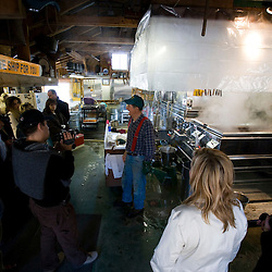 Paul Messer, Sr. explains how he makes maple syrup to a tour group in his sugar house in Orford, New Hampshire.  Sunday Mountain Maple Farm.