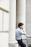 Businessman on cell phone outside building sitting on pillar