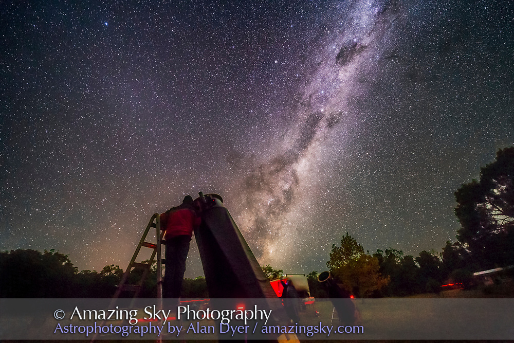An observer (me!) at one of the large Dobsonian telescopes at the 2017 OzSky Star Party while the Dark Emu rises in the east in the sky.as a backdrop. <br />