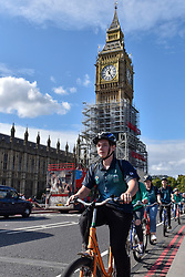 © Licensed to London News Pictures. 30/09/2017. London, UK. Tourists cycle by the Elizabeth Tower, covered in scaffolding and home of Big Ben, as remedial work continues.  A new statement released by Parliament states that the cost of renovations has more than doubled to £61m as contractors have found the work to be more complex and extensive compared to the 2016 estimate of £29m.  Photo credit : Stephen Chung/LNP