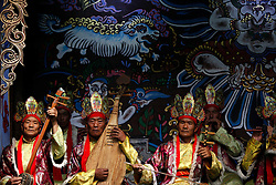Musicians of the Naxi ethnic minority performing in front of Naxi art murals in a culture show, the Naxi Impression Show in Lijiang, Yunnan Province, China, 04 April 2012. The Naxi ethnic minority  group is one of the main ethnic minority groups settled in Lijiang, Yunnan province with a unique culture and traditions. The religious Dongba scriptures of the Naxi has been recognised as World Memory Heritage by UNESCO in 2003.