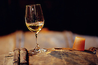 November 2001, Chablis, France --- glass of white wine (Chablis) sitting next to a rubber cork on an aging barrel in a wine maker's cellar --- Image by © Owen Franken/CORBIS