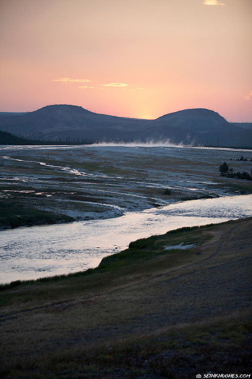 The sun sets behind the mountains beyond Midway Geyser Basin and the Firehole River in Yellowstone National Park.