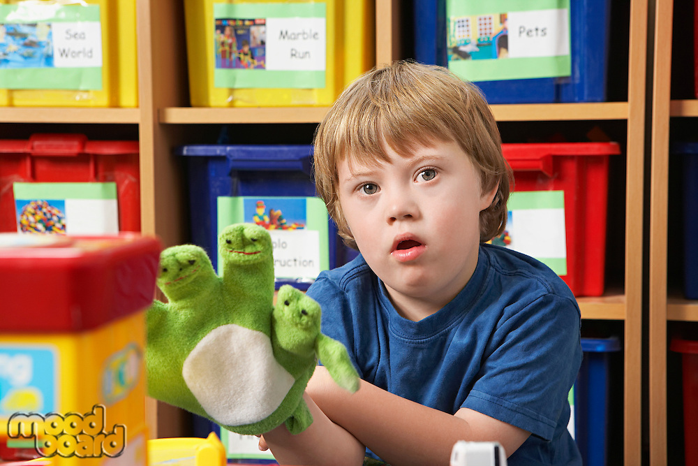 Portrait of boy (5-6) with Down syndrome playing with finger puppets in kindergarten